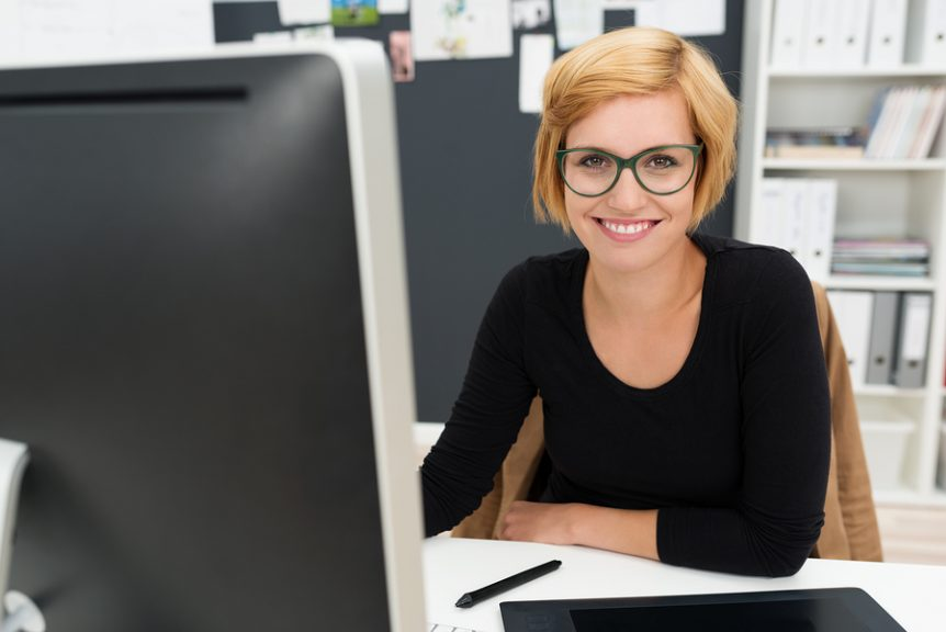 Friendly attractive young businesswoman sitting at her desk in the office smiling at the camera past her computer monitor